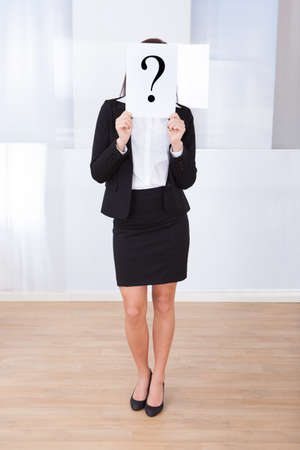 Full length of young businesswoman holding question mark sign in front of her face at office photo