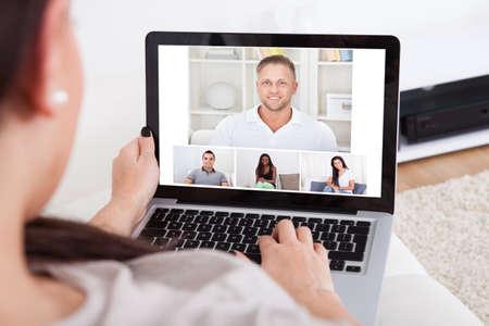 Bijgesneden afbeelding van een jonge vrouw met behulp van laptop voor videoconferentie thuis