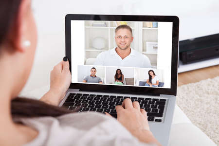video conference: Cropped image of young woman using laptop for video conference at home Stock Photo