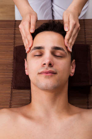head massage: High angle view of young man receiving head massage from massager in spa