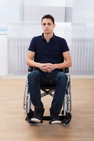 Full length portrait of young handicapped man sitting on wheelchair at home photo