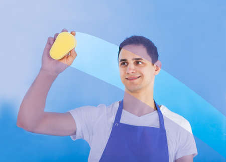 Portrait of young male servant cleaning glass with sponge over blue background photo