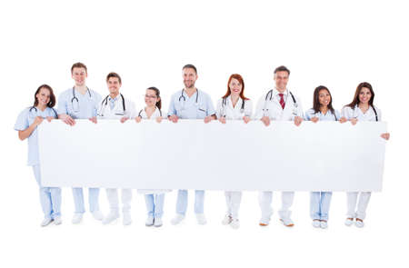 Large group of doctors and nurses holding a long blank white banner with copyspace for your text isolated on white photo