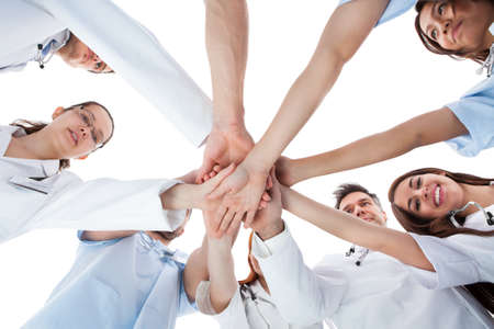 doc: Doctors and nurses stacking hands. Isolated on white