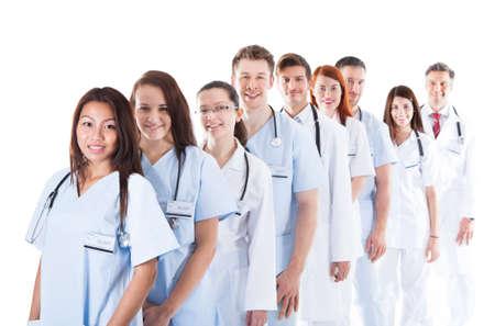 Lange terugwijkende lijn of rij van lachende artsen en verpleegkundigen in het wit uniform dragen stethoscopen rond hun nek geïsoleerd op wit