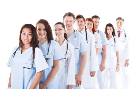 Long receding line or queue of smiling doctors and nurses in white uniforms wearing stethoscopes around their necks isolated on white Stock Photo