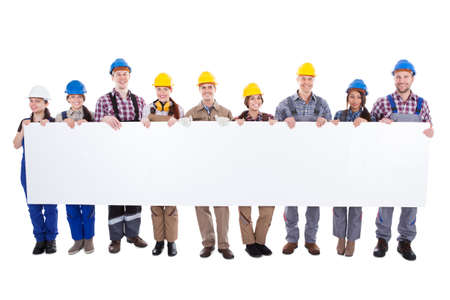 artisan: Large diverse multiethnic group of workmen and women standing in a line holding a long blank white banner with copyspace for your text isolated on white