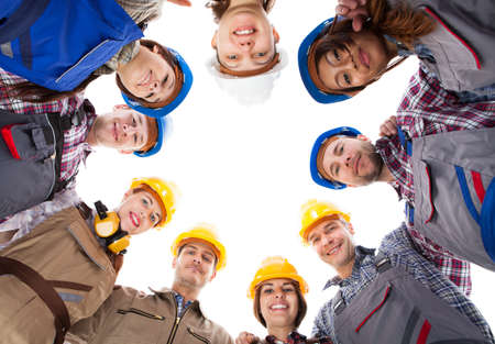 Large group of construction workers standing in circle. Isolated on white Stock Photo