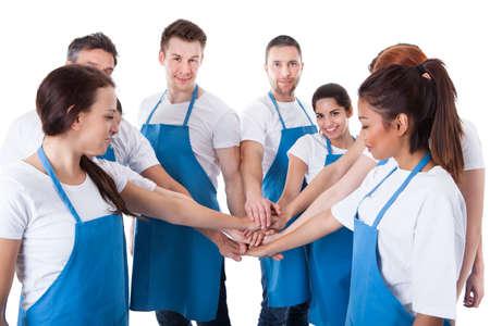 cleaning team: Gran grupo de limpiadores de apilamiento manos. Aislados en blanco
