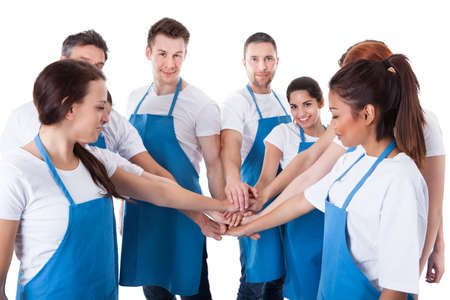 join the team: Large group of cleaners stacking hands. Isolated on white