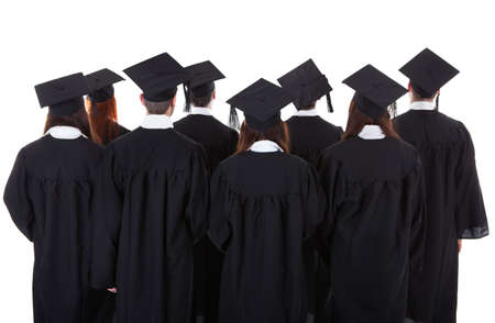 Large group of students graduating standing in the gowns and mortarboard hats viewed from behind isolated on white