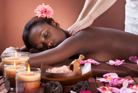 Side view of young woman receiving shoulder massage at spa salon photo