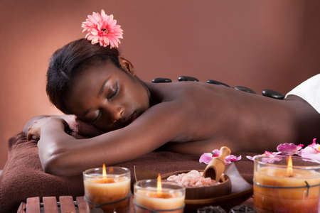 Young woman undergoing lastone therapy at beauty spa photo