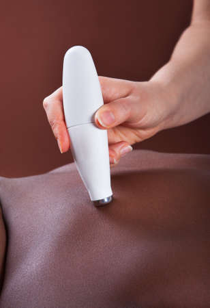 Close-up view of young African American woman undergoing microdermabrasion therapy at beauty spa photo