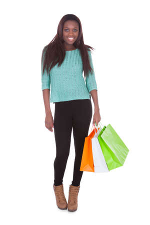 Full length portrait of African American woman carrying shopping bags against white background Stock Photo - 27393827