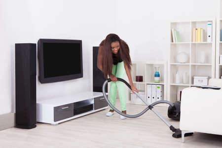 Full length of young woman cleaning home with vacuum cleaner Stok Fotoğraf