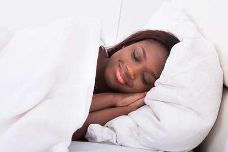 jeune fille: Sourire femme afro-am�ricaine � dormir dans son lit