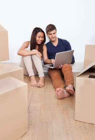 Young multiethnic couple using laptop together while sitting on floor in new home photo