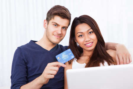 Portrait of smiling young couple with laptop and credit card shopping online at home photo