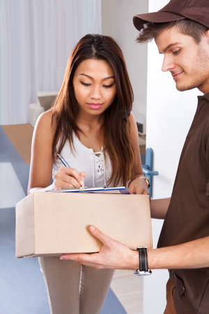 Young woman signing while receiving courier from delivery man at home photo