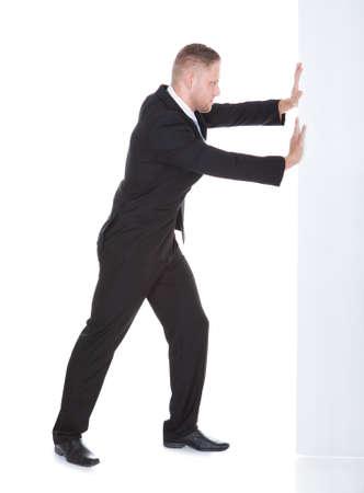 Zakenman duwen de rand van een leeg wit teken leunend zijn gewicht tegen haar volle lengte op witte met alleen de rand van het bord zichtbaar