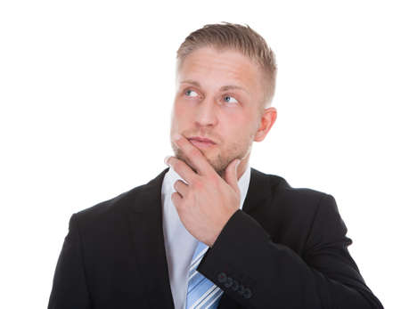 deep thought: Businessman standing deep in thought with his hand to his chin looking up into the air with a look of contemplation isolated on white with copyspace