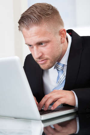 busy beard: Businessman leaning forward staring intently at his laptop screen as he types information on the keyboard while sitting at his desk  close up portrait Stock Photo