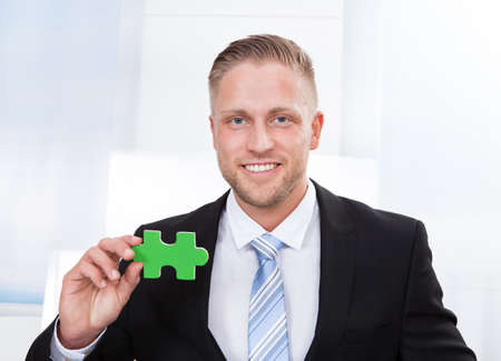 overcome a challenge: Successful businessman holding a green puzzle piece as he indicates he has solved a problem  come up with an inspirational idea or overcome a challenge  white textured background