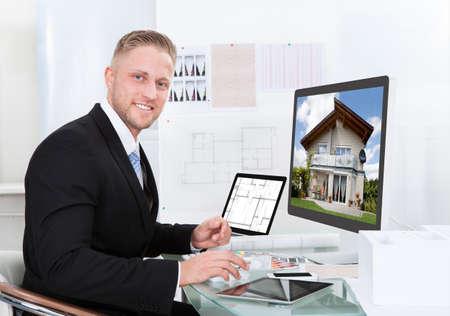 ビジネスマンや不動産エージェント デスクトップ モニターに目に見える民家の外観を見て、オフィスで彼の机に坐っている間オンライン ポートフ