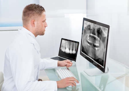 Doctor or radiologist looking at an x-ray online displayed on a desktop monitor as he makes a diagnosis or checks prognosis photo