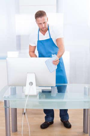 desinfectante: Conserje joven y guapo o limpiador de limpieza de una oficina de la pulverizaci�n de la parte superior de la mesa con un desinfectante antes de que los trabajadores de la oficina comienzan su d�a
