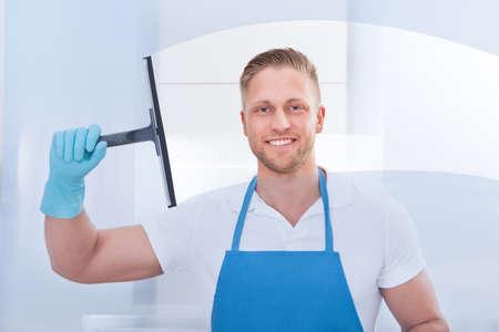 desinfectante: Conserje Hombre usando una escobilla de goma para limpiar una ventana en una oficina con un delantal y guantes mientras trabaja