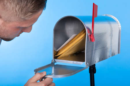 mail marketing: Man opening his mailbox to remove mail inside  close up of his hand on the open door against a blue sky
