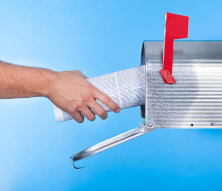mass media: Man removing a newspaper from his mailbox with a closeup of his hand clasping the folded paper against a blue sky Stock Photo