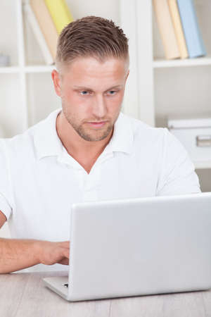 short sleeved: Young man in a short sleeved shirt sitting working at home on a laptop in a home office