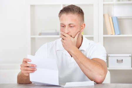 perturbed: Businessman sitting in an office reacting in shock to the contents of a letter that he is reading raising his hand to his mouth
