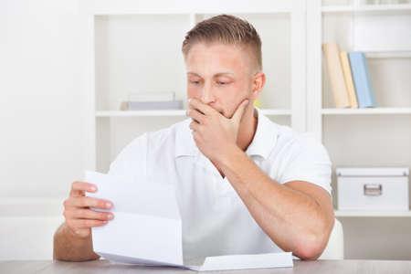 preocupacion: Hombre de negocios sentado en una oficina de reaccionar en estado de shock al contenido de una carta que él está leyendo llevándose la mano a la boca