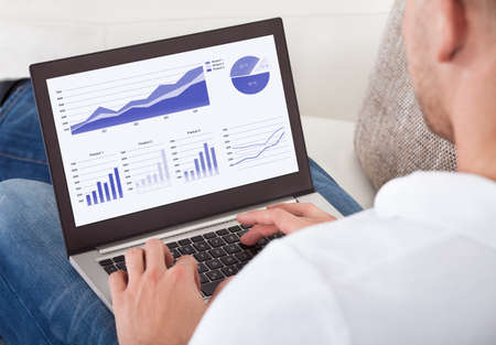 over the shoulder: Over the shoulder view of the screen of a businessman analyzing graphs on his laptop Stock Photo