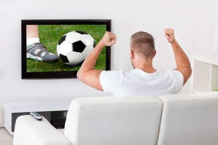 サッカーのファンのように彼は彼のリビング ルームで快適なソファに座っている彼の頭の上にサッカー ボールを保持テレビで試合を見て興奮してく 写真素材