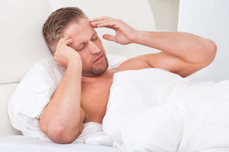 sore eye: Man waking up with a nasty headache from overindulgence or illness wincing in pain and raising his hands to his head Stock Photo