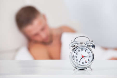 somnolence: Alarm clock about to ring in the morning showing a quarter past seven with a man sleeping in bed in the background  focus to the clock
