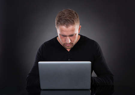 retrieves: Man or hacker working on a laptop computer at night bending forwards over the keyboard in the glow from the screen as he browses the internet or retrieves and downloads personal data
