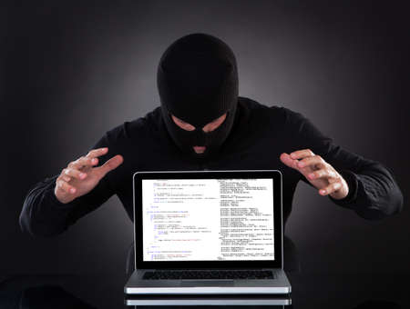 Hacker in a balaclava standing in the darkness furtively stealing data off a laptop computer or inserting spyware in an online security and risk concept photo