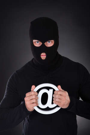 Hacker dressed in black wearing a balaclava with a white internet domain symbol in his hands as he stands in darkness conceptual of online safety and security and cyber crime photo