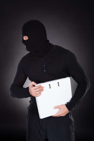 corporate espionage: Thief in a balaclava stealing a file with information as he furtively makes his escape in the darkness  conceptual of data and identity theft Stock Photo