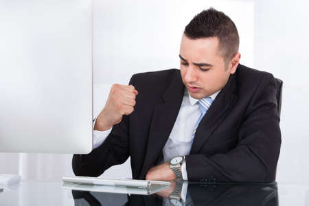 Stressed young businessman clenching fist at computer desk in office photo