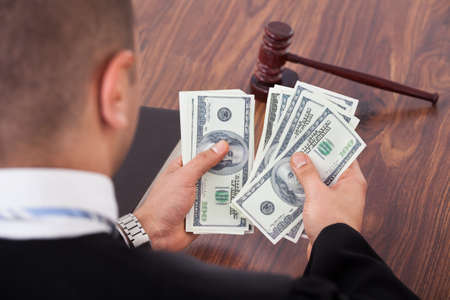 Rear view of male judge counting dollars in courtroom photo