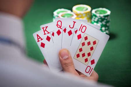 Cropped image of man playing winning hand of poker photo