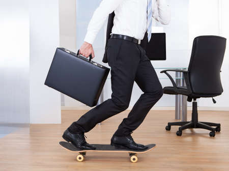 Side view of young businessman on skateboard in office photo