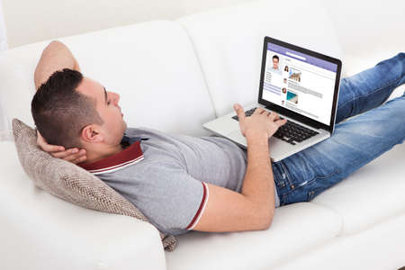 Young man chatting on laptop while lying on sofa at home photo